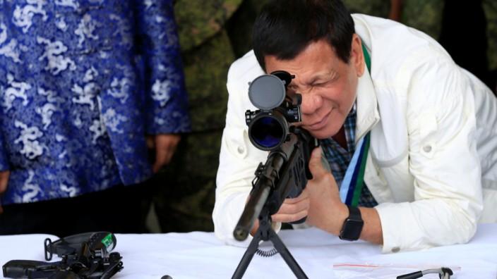 Duterte checks sniper rifle during ceremony at Clark Air Base, near Angeles City