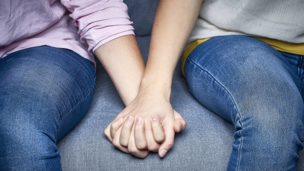 Partial view of lesbian couple holding hands on couch PUBLICATIONxINxGERxSUIxAUTxHUNxONLY DISF002271