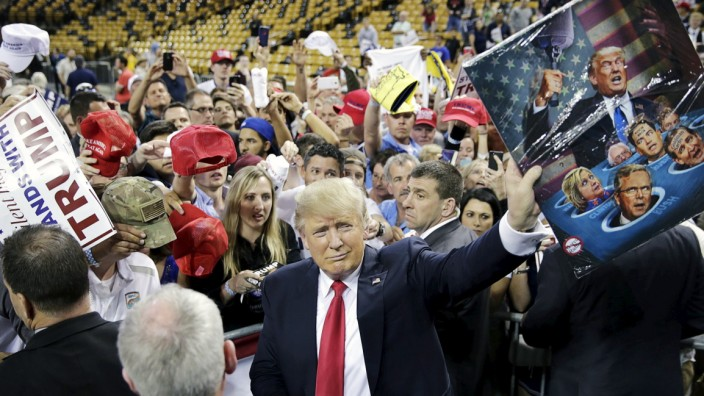 Republican U.S. presidential candidate Donald Trump showing off a painting a supporter gave him at a campaign rally held at the University of Central Florida in Orlando