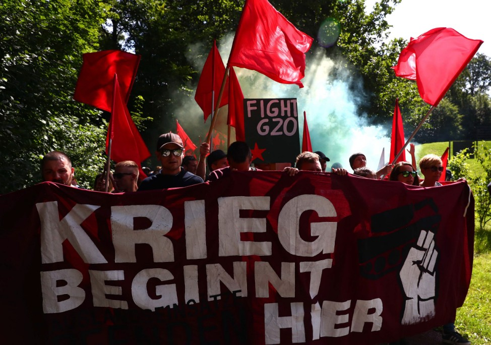 Activists carry a banner reading 'The war starts here' as they march to their camp during the G20 summit in Hamburg