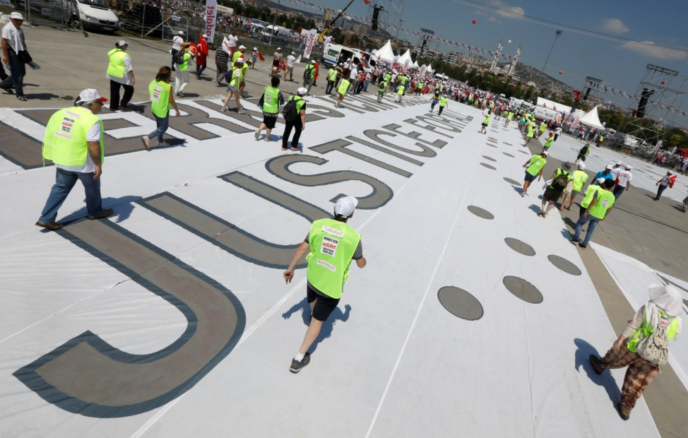 People walk over a  huge banner during a rally to mark the end of the main opposition CHP leader Kilicdaroglu's 25 day of protest, dubbed 'Justice March', against the detention of the party's lawmaker Berberoglu, in Istanbul