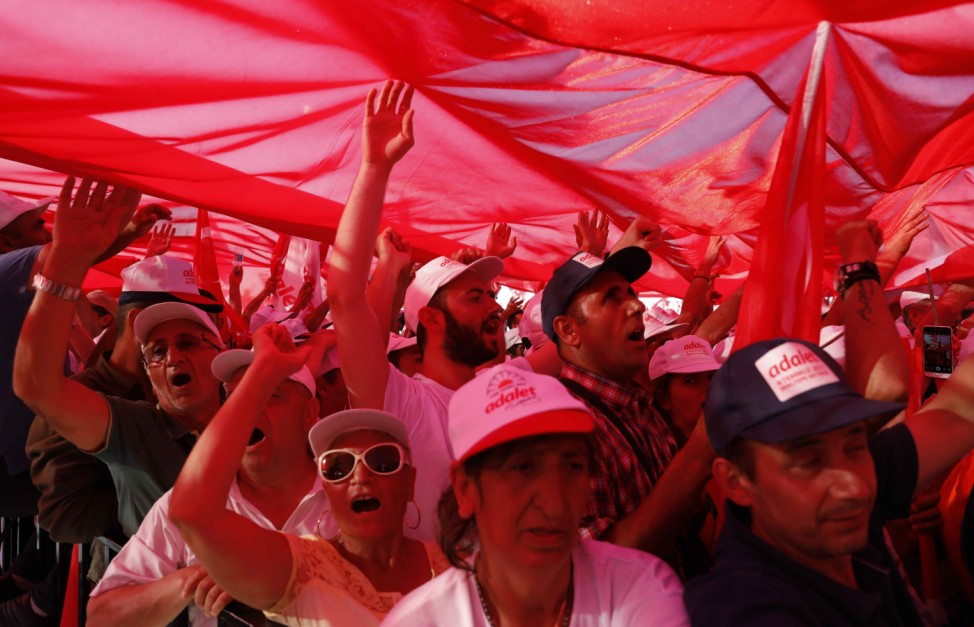 People carry a huge Turkish flag during a rally to mark the end of the main opposition CHP leader Kilicdaroglu's 25-day long protest, dubbed 'Justice March', against the detention of the party's lawmaker Berberoglu, in Istanbul