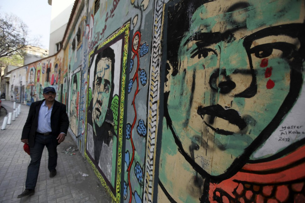 Egyptian man walks in front of a wall sprayed with graffiti depicting images of the martyrs of the Egypt revolution in Cairo