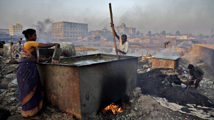 Workers boiling leather wastes to make glue at Hazaribagh area by the side of the Buriganga river