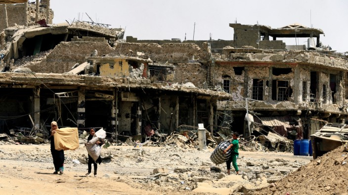 Civilians carry their belongings as they walk between destroyed buildings by clashes in the Old City of Mosul