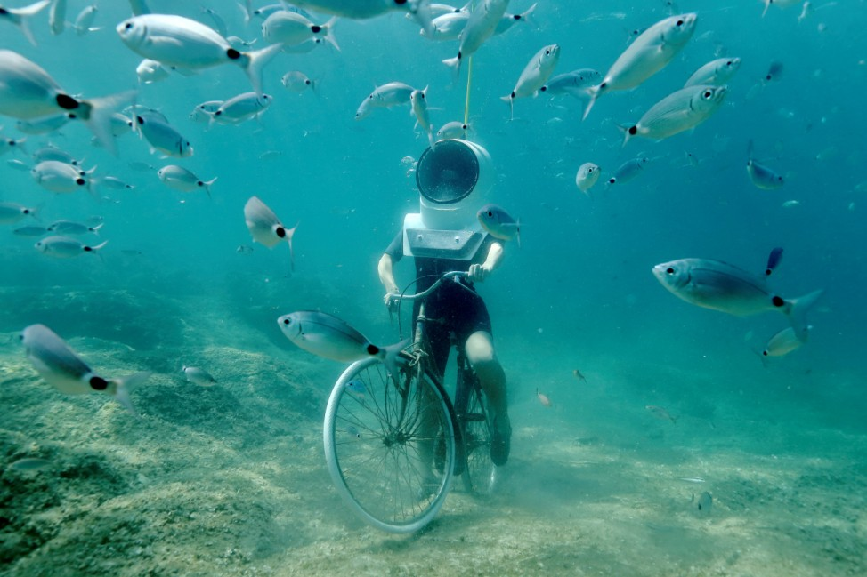 A woman dives and pretends to ride a bike in Underwater Park in Pula