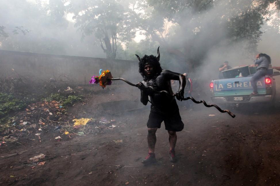 A devotee covered in motor oil takes part in the festivities honouring the capital's patron saint Santo Domingo de Guzman in Managua