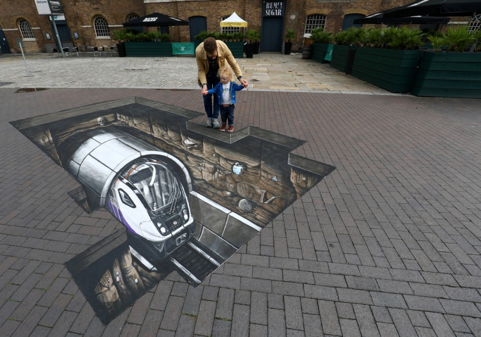 Mike Clueless and son Elliot pose by a piece of Crossrail themed 3D artwork during a photocall at the Museum of London Docklands in London