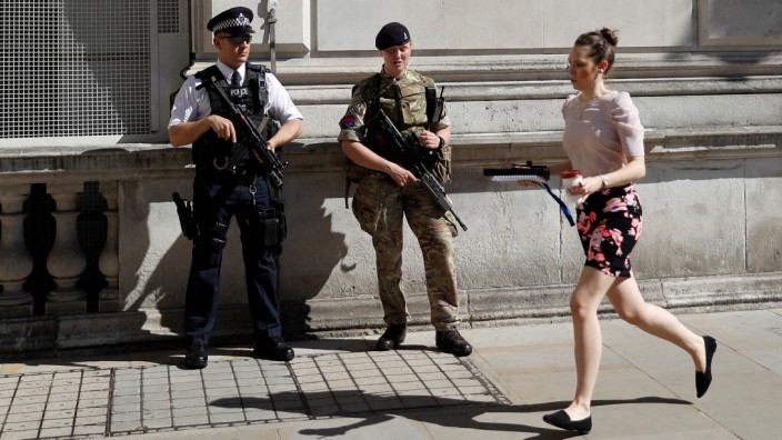 A woman rushes past a soldier and an armed police officer on duty on Whitehall in London