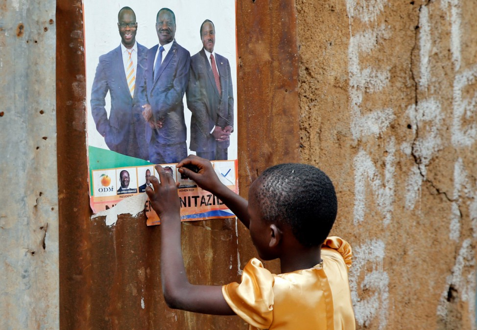A child stands outside their house pasted with ripped campaign posters ahead of the Presidential election at the Kisumu Ndogo village in Kibera slums of Nairobi