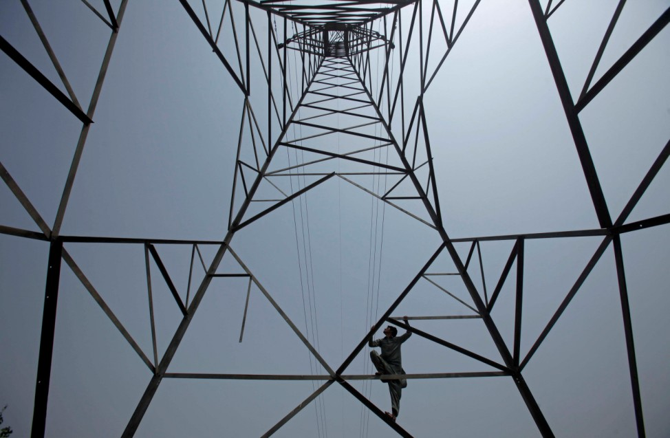 A worker of PESCO climbs up a high-voltage pylon in Peshawar