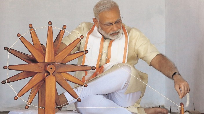 India's PM Modi spins cotton on a wheel during his visit to Gandhi Ashram in Ahmedabad