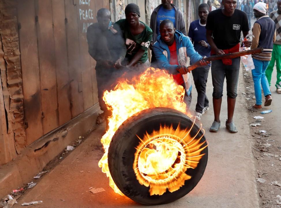 Supporters of opposition leader Raila Odinga set up flaming tyre barricade in Kibera slum in Nairobi
