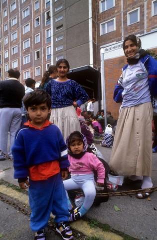 Reportage Ausschreitungen Rostock Lichtenhagen 1992 auf dem Gehweg ausharrende Flüchtlingsfamilie