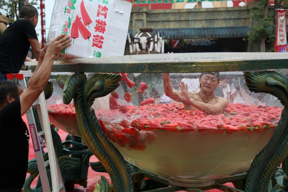 A man sits in a water vat filled with red chilies as he takes part in a chili-eating competition at a scenic area in Ningxiang