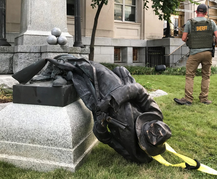 A Sheriff's deputy stands near the toppled statue of a Confederate soldier in front of the old Durham County Courthouse in Durham