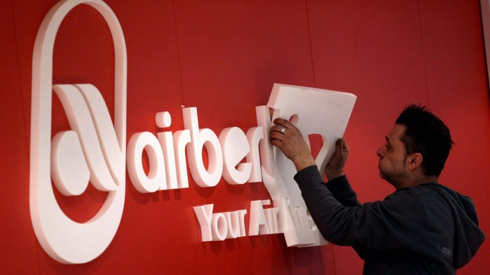 A worker puts finishing touches on booth of Air Berlin in Berlin