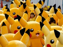 A staff guides performers wearing Pokemon's character Pikachu costumes as they prepare for a parade in Yokohama