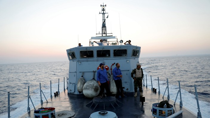Members of the Libyan Coast Guard search for migrants off the coast of Tripoli