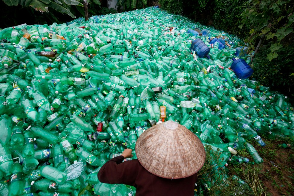 A woman sorts out recyclable plastic soft drink bottles at Xa Cau village, outside Hanoi