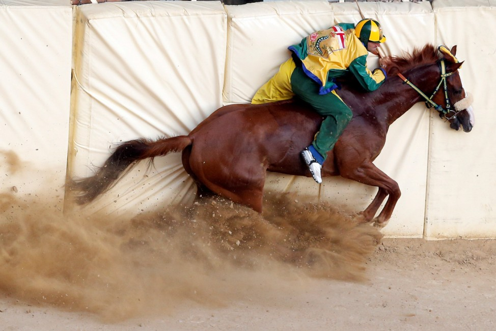Jockey Luigi Bruschelli of the 'Bruco' (Caterpillar) parish crashes during the Palio of Siena horse race
