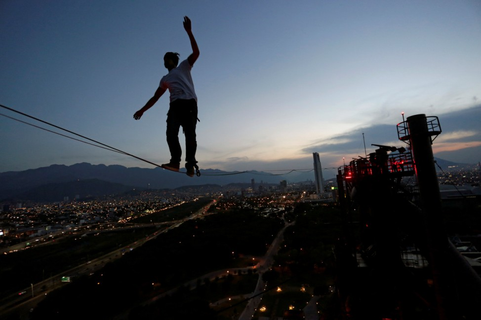 A slackliner crosses a high wire between two chimneys of the structure housing former foundry Horno Alto No. 3, at Fundidora park in Monterrey