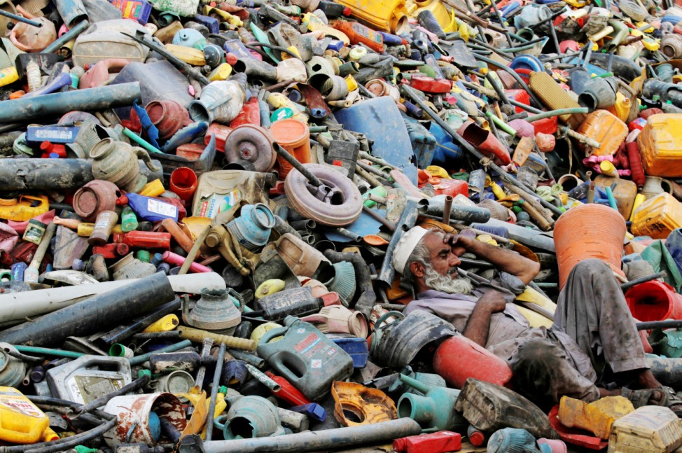 A labourer rests over a pile of recyclables at a yard in Peshawar