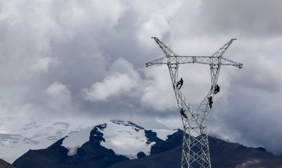 Technicians work on an electricity pylon in the mountains near Mengda village