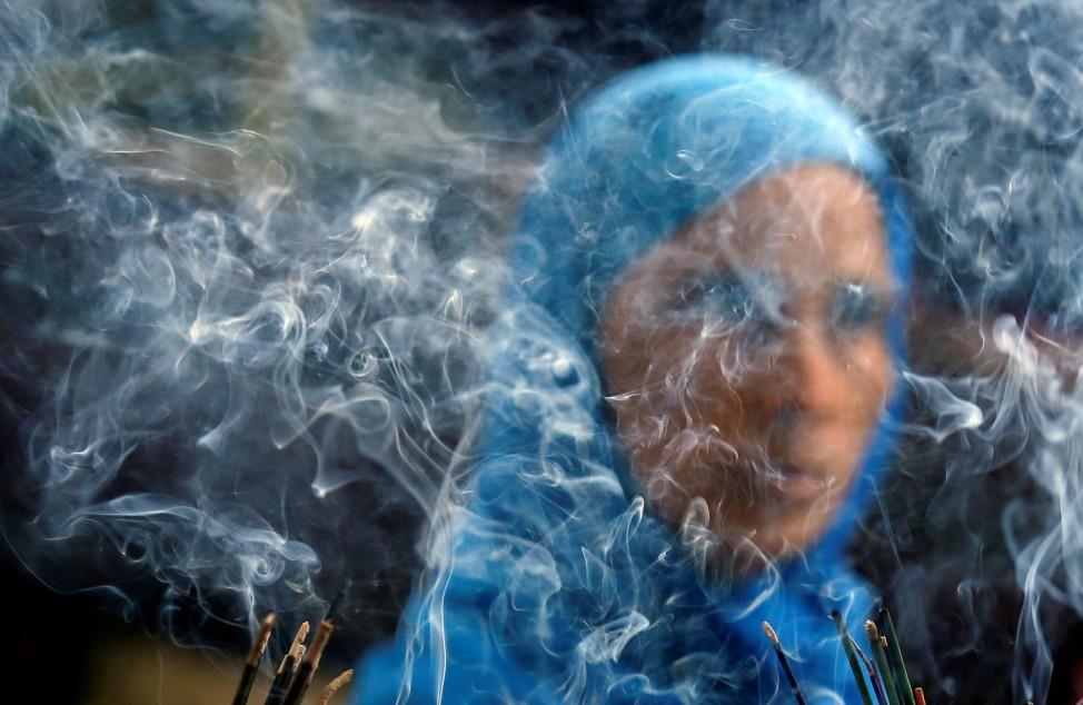 Smoke rises from burning incense sticks as a woman prays inside the shrine of Muslim Sufi Saint Nizamuddin Auliya in New Delhi