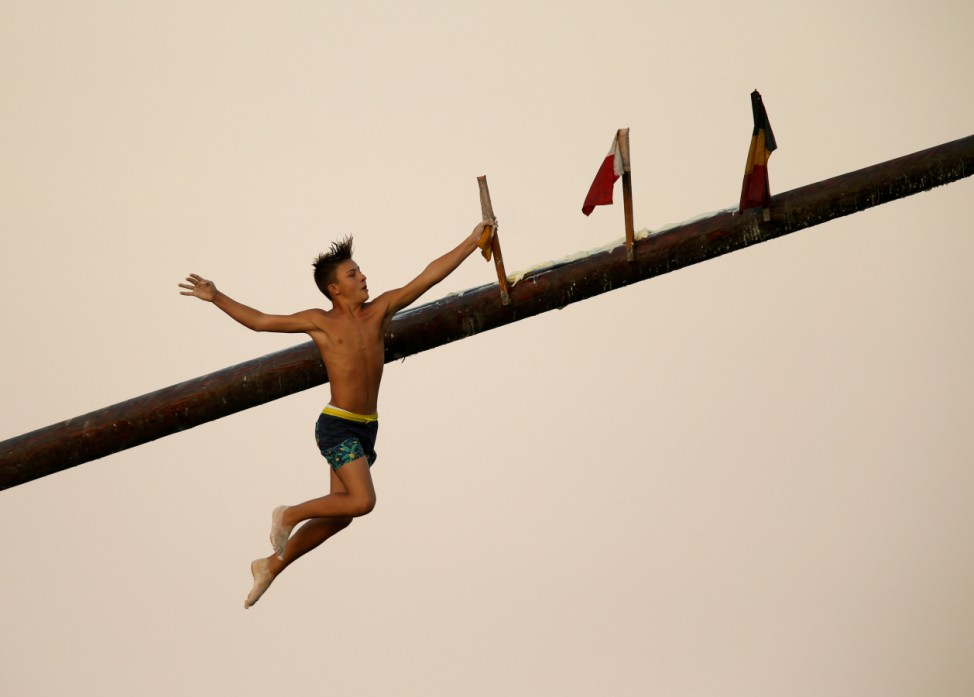 A child competitor grabs a flag as he falls off the 'gostra', a wooden pole covered in lard, during the celebrations for the religious feast of St Julian, patron of the town of St Julian's