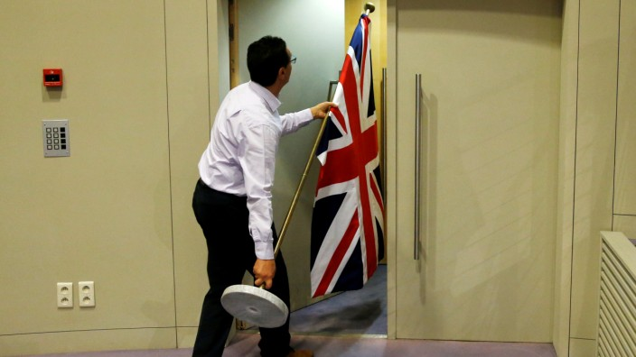 FILE PHOTO: An official carries a Union Jack flag ahead of a news conference by Britain's Secretary of State for Exiting the European Union Davis and EU's chief Brexit negotiator Barnier in Brussels