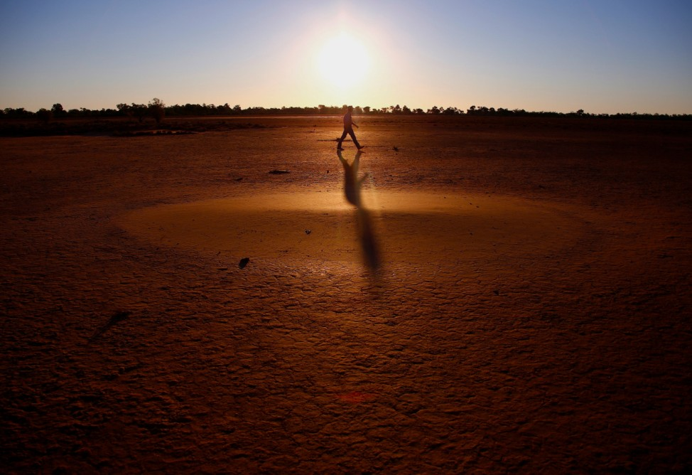 Farmer Tony Reid casts a shadow as he walks across a claypan while inspecting a paddock on Kahmoo Station property, located on the outskirts of the south-western Queensland town of Cunnamulla in outback Australia