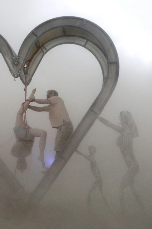 Burning Man participants perform a shibari rope scene during desert dust storm at the Burning Man festival in the Black Rock Desert of Nevada