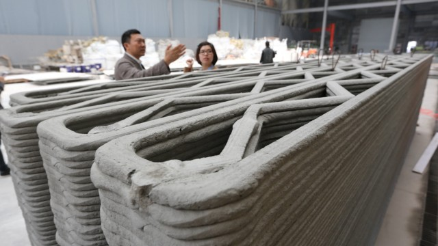 The inventor of 3D printed house Ma Yihe L shows the 3D printed walls of a house in Shanghai east