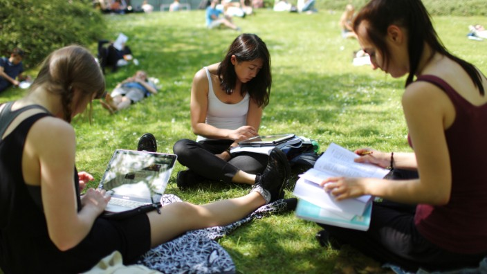 Students sit on grass at the campus of the Free University of Berlin 'Freie Universitaet Berlin' in Berlin