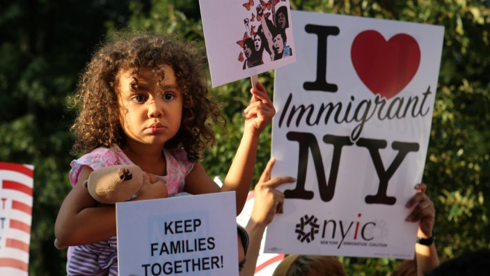 A girl sitting on the shoulders of her father holds a sign reading 'Keep Families Together' at a protest against U.S. President Donald Trump's proposed end of the DACA program that protects immigrant children from deportation in New York City