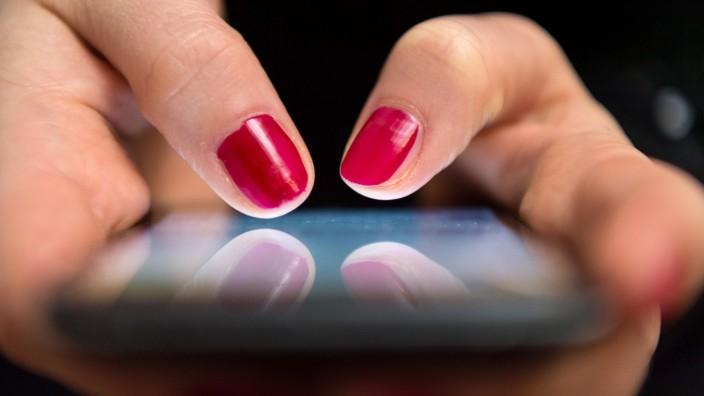 Frau tippt auf einem Smartphone