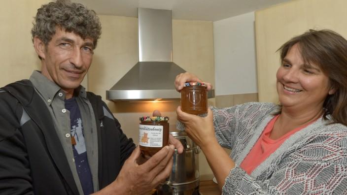 Unterhaching: Es läuft zäh, und das ist gut so. Claudia Köhler, Mitinitiatorin des Krautgarten-Projekts, assistiert Imker Johannes Fagner beim Honigabfüllen.