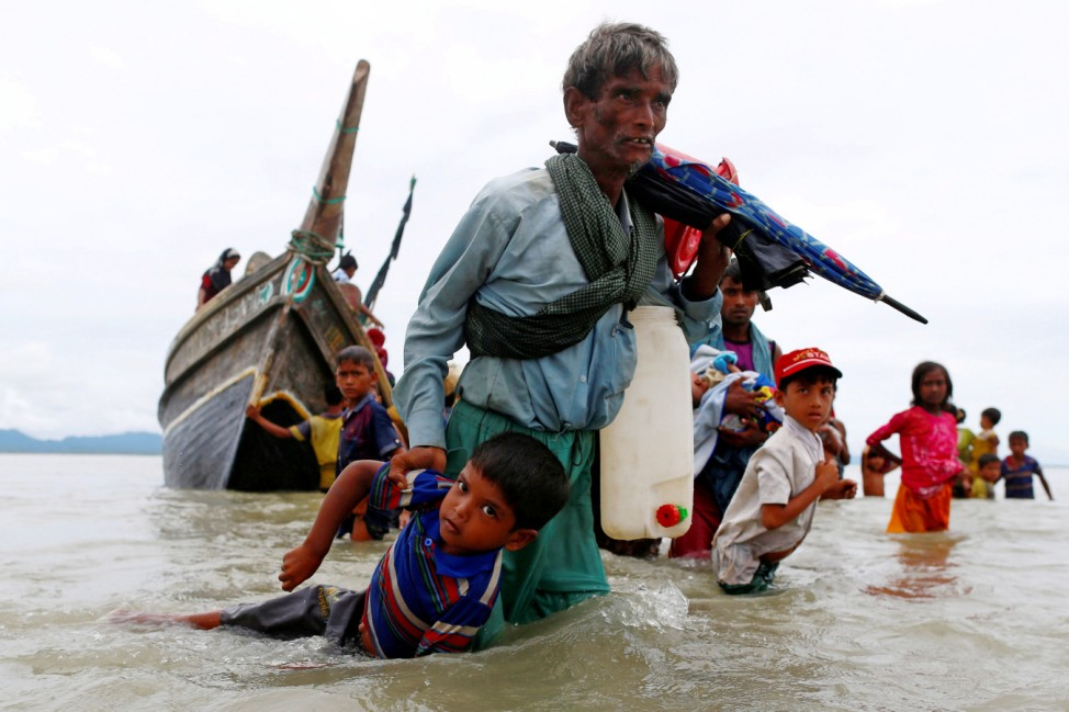 A Rohingya refugee man pulls a child as they walk to the shore after crossing the Bangladesh-Myanmar border by boat through the Bay of Bengal in Shah Porir Dwip
