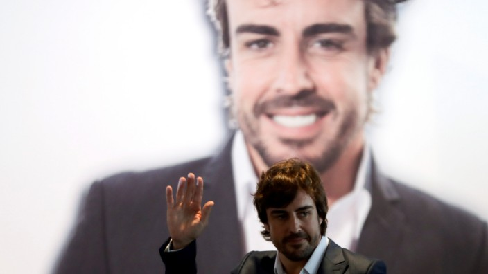 McLaren's Alonso waves as he arrives with Real Madrid's President Perez for a ceremony to name him Real Madrid honorary member at Santiago Bernabeu stadium in Madrid