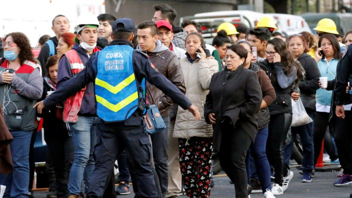 A police officer and people wait along the street after a tremor was felt in Mexico City