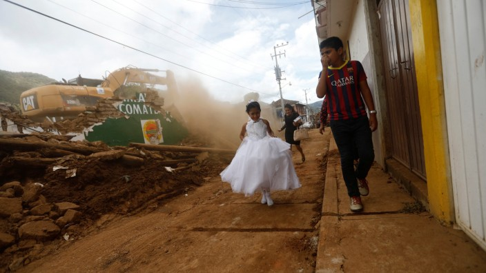 A girl in a communion dress walks past a demolition machine tearing down a house damaged by an earthquake, in Tecomatlan