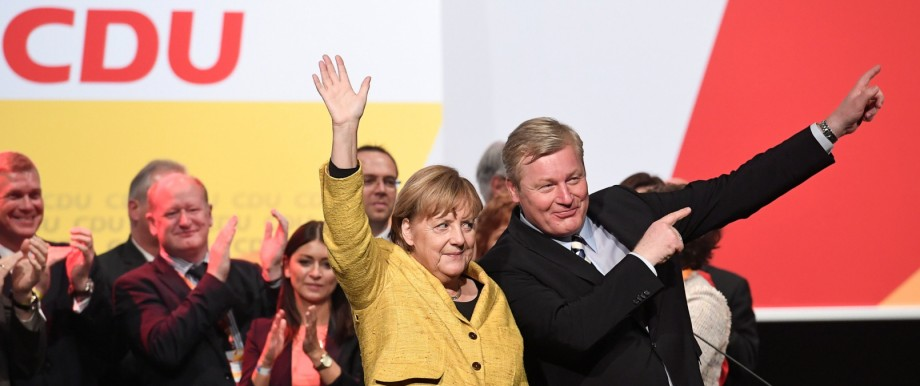 German Chancellor Angela Merkel and Lower Saxony's Christian Democratic Union's (CDU) top candidate Bernd Althusmann wave after a regional election campaign in Hildesheim