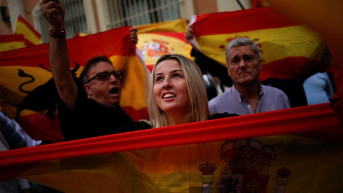Demonstrators hold up Spanish flags during a gathering in support of Spanish civil guards outside their barracks in Barcelona