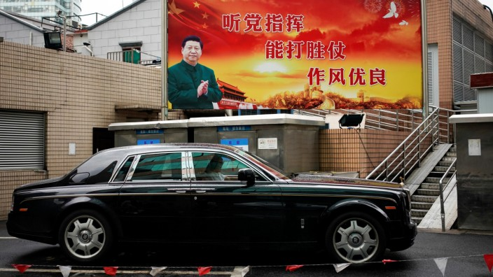 A poster with a portrait of Chinese President Xi Jinping overlooks a street in Shanghai