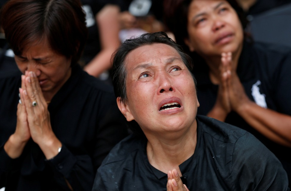 Mourners react as the Royal Urn of late King Bhumibol Adulyadej is carried by the Great Victory Chariot during a royal cremation procession at the Grand Palace in Bangkok