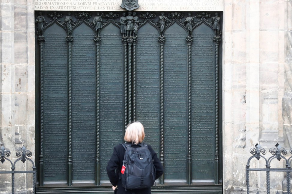 A woman looks at German theologian Martin Luther's theses door during the 500th Anniversary of the Reformation at the Castle Church in Wittenberg