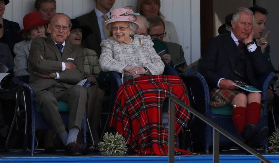 FILE PHOTO: Britain's Queen Elizabeth together with her husband Prince Philip and her son Prince Charles react as they watch an event at the Braemar Highland Gathering in Braemar, Scotland