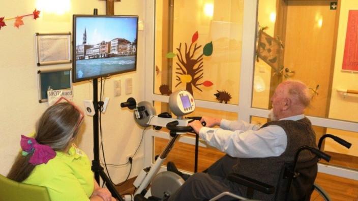 Bessere Ausstattung im Pflegeheim der Caritas: Am Ergometer trainieren und gleichzeitig am Bildschirm Städte erkunden - das trainiert Muskeln und Geist.