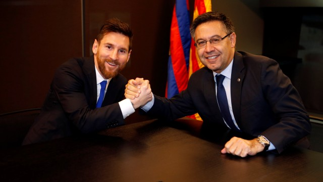 Barcelona's Argentine superstar Lionel Messi poses with FC Barcelona president Josep Maria Bartomeu during the signing of his new contract in Barcelona
